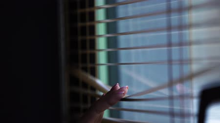persiana : Cute young blond woman in white shirt looking through Venetian blinds