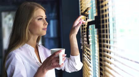 persiana : Delicious tea at the morning. Portrait of blond contemplating young pretty lady with white cup looking out the window Stock Footage