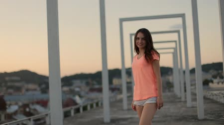шорты : Sexy brunette model in orange t-shirt and blue shorts walking and posing on the urban city background at sunset