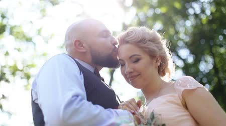 krokus : Sensual close up portrait of handsome groom kissing forehead of his beautiful bride, outdoors