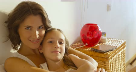 мама : Beautiful mother hugs her cute daughter and smile, at home interior close-up