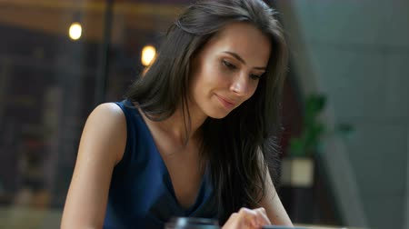 restaurante : Working at the cafe. Young beautiful long hair woman sitting at the table and using tablet computer in outdoor cafe Stock Footage