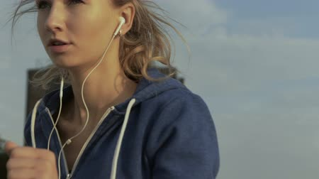 trabalhar fora : Serious young woman listening to music in her earphones, while running near the sea.