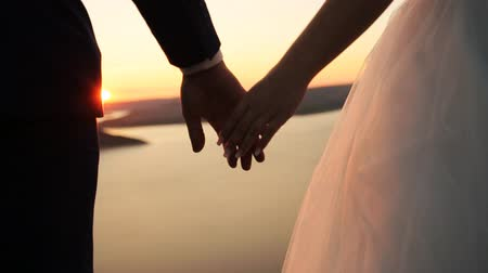 weddings : Loving couple holding hands , while watching beautiful sunset.
