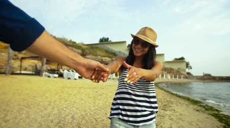caminhada : Close up of young happy woman in sunglasses and hat , holding hand of her boyfriend. Vídeos
