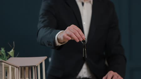 vista frontal : Slow motion of males midsection in formal jacket holding house keys in hand and showing to camera. Real-estate agent offering home keys to clients at table. Keys with wooden house shaped key ring.