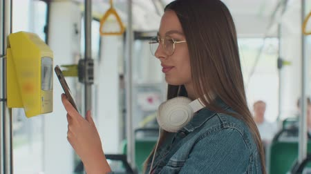 pagante : Portarit of a young smiling woman paying conctactless with smartphone for the public transport in the tram.