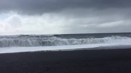 Large waves crashing into the Black sand beach of Vik in Iceland, this beach is known to be deadly and has killed people in the past Stock mozgókép