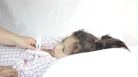 horečka : Sick girl lying on bed and her mother take good care, High fever