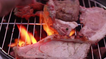 bbq grill : Porkchop, beef steak on flaming and smoking grill Stock Footage
