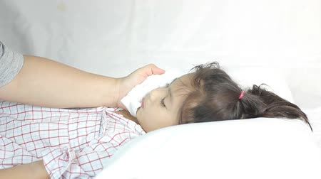 doente : Sick girl lying on bed and her mother take good care, High fever