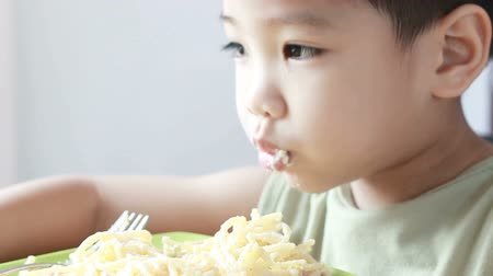 HD footage of Asian boy with fork in hands eats pasta, close-up
