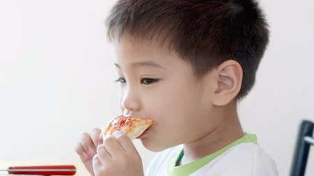 фастфуд : HD footage close up of cute Asian boy eat pizza