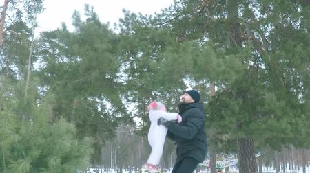 śnieżka : Dad throws his daughter up to the sky in the winter forest, slow motion