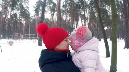 anne : Mom holds her daughter in the winter forest