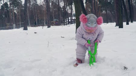 házení : A little girl in a red hat with big bamboons sculpts a snowball with a light green snowy glitter