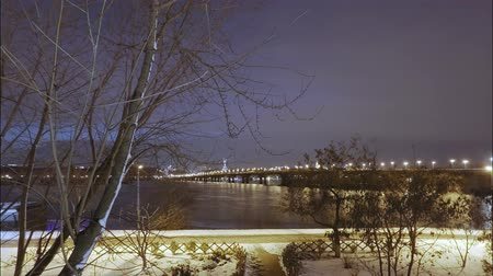 kolínská voda : Time lapse. Late sunset on a cloudy day in a snowy winter, a view of the Dnieper River and the Patona Bridge, passersby walk, clouds and waves float on the river