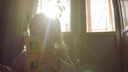 dazzle : Little beautiful sweet girl with blond long hair pulls puzzles on the background of the sun, the suns rays over her head