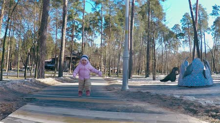 havlama : A little girl in a pink jacket and striped hat runs along the path in the spring park in the moms embrace and smiles Stok Video