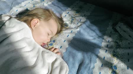 crying baby : A little girl with blond hair is sleeping on the bed and lit by sunlight. Stock Footage