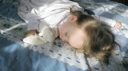 peluş : Beautiful little girl with blond hair sleeping on the bed and lit by the sun, hugging a plush bunny