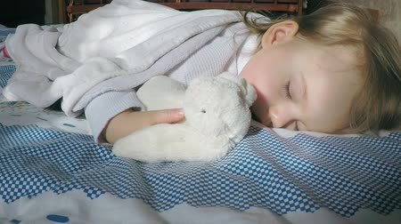 матрац : Cute little girl with blond hair sleeps on the bed on her tummy lit by the sun with a teddy bunny hugging Стоковые видеозаписи