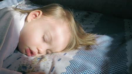 matrace : Beautiful little girl with blond hair sleeping on the bed and lit by the suns rays covered with a beige blanket