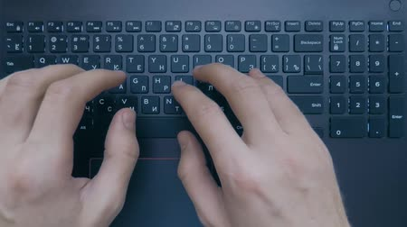 yazar : Two hands are typing on a laptop keyboard, top view, slow motion