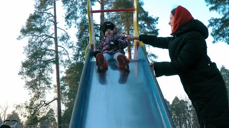 childrens : A little girl in a colorful jacket moves down from a multi-colored slide with the help of her mother in the spring park on a background of pine trees