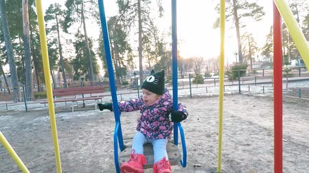 childrens : A little girl in a colorful pink jacket and black hat is riding on a swing over a puddle on the playground in the park-forest in early spring and smiles
