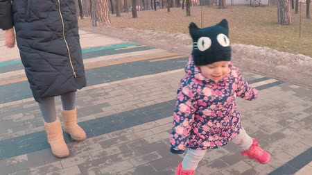 dino : Little cute girl in a colorful pink jacket draws with a young mother with chalk on a pavement near the playground in a park on the outskirts of the forest during sunset in early spring