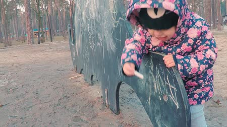 linden : Little cute girl in a colorful pink jacket draws with chalk on a blackboard in the form of a dinosaur on a childrens playground in a park on the outskirts of the forest during sunset in early spring