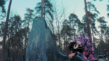 borowina : Little cute girl in a colorful pink jacket draws with chalk on a blackboard in the form of a dinosaur on a childrens playground in a park on the outskirts of the forest during sunset in early spring