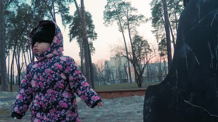 cam : Little cute girl in a colorful pink jacket draws with chalk on a blackboard in the form of a dinosaur on a childrens playground in a park on the outskirts of the forest during sunset in early spring