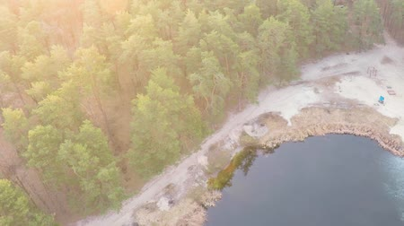 backround : Aerial view of a lake in a pine forest with a sandy beach in early spring at sunrise