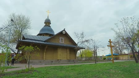 passerby : 4K time-lapse. The wooden church in the old Russian style with a golden cross in the park of the city of Kiev