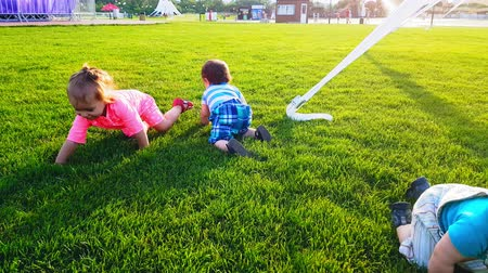 sakk : Three babies crawling on the bright green grass on a warm summer day