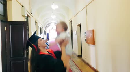 graduação : Graduate girl with her child in the university corridor
