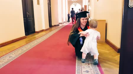 diploma : Graduate girl with her child in the university corridor