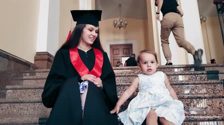 diplom : Graduate girl with her child in the university corridor