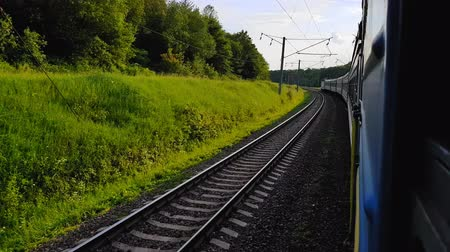 archívum : The passenger train returns to the left. The view from the window of the car, bus, train. Journey from the train on a sunny day Stock mozgókép