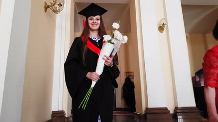 master's degree : Beautiful girl graduate master goes up the stairs with flowers at the university