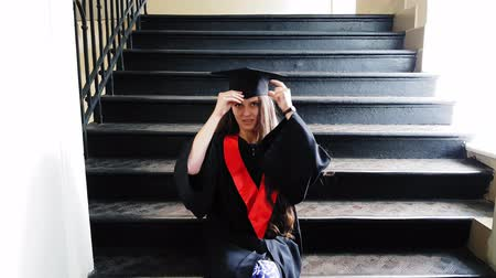 master's degree : Beautiful student graduate master tapes her leg with a plaster while sitting on metal steps at the university