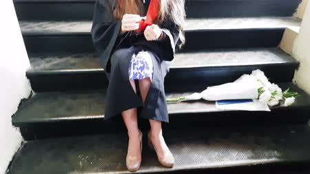 grãos : Beautiful student graduate master tapes her leg with a plaster while sitting on metal steps at the university