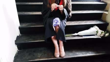 commencement : Beautiful student graduate master tapes her leg with a plaster while sitting on metal steps at the university