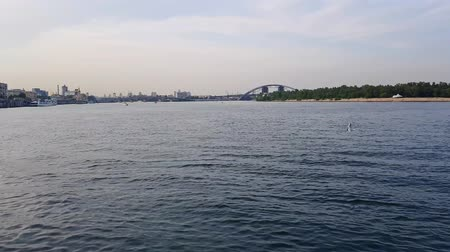catamaran : 4K, the ship sails on the wide river of the Dnieper with large bridges before the sunset