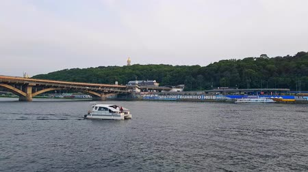 navigation : 4K, the ship sails on the wide river of the Dnieper with large bridges before the sunset