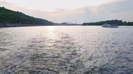 pleasure boats : 4K, the ship sails on the wide river of the Dnieper with large bridges before the sunset
