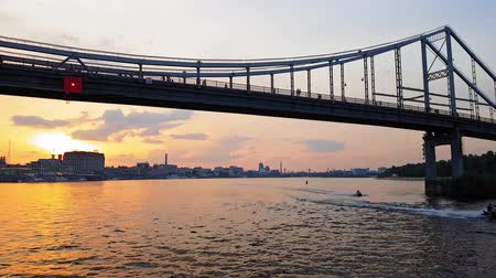 motorbot : 4K. The ship sails on the wide river Dnieper with large bridges before sunset