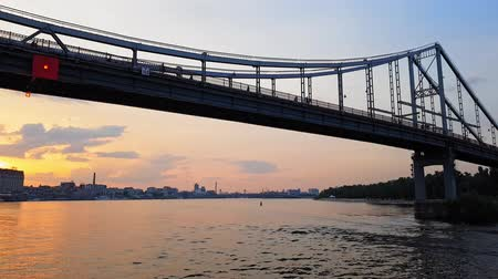 puente peatonal : 4K. The ship sails on the wide river Dnieper with large bridges before sunset